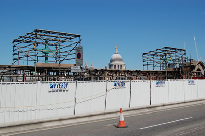 Scaffolding surrounding the street lighting with the dome of St. Paul's Cathedral in the background