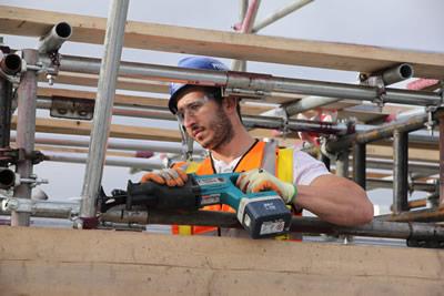 Scaffolder, cutting a scaffolding pole to size